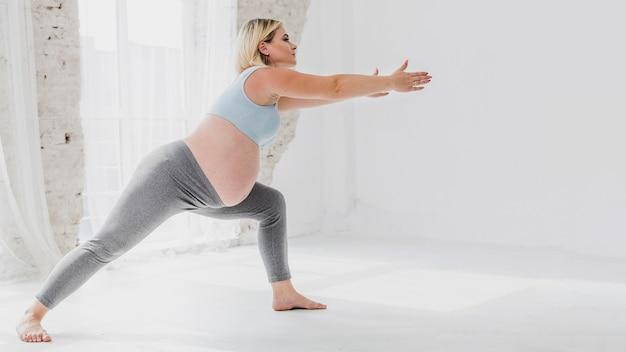 Vista lateral mulher grávida fazendo exercícios Foto gratuita