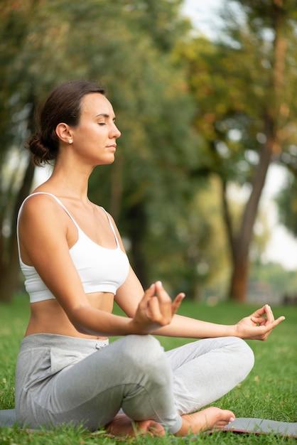 Vista lateral mulher meditando com os olhos fechados Foto gratuita