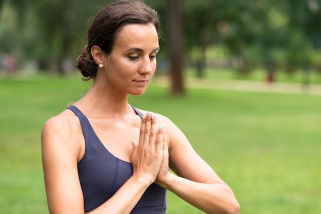 Vista lateral mulher meditando gesto com a mão Foto gratuita