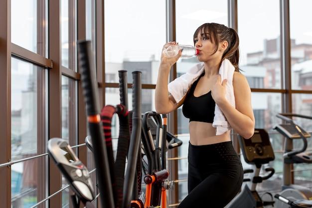 Vista lateral mulher na academia de hidratação Foto gratuita