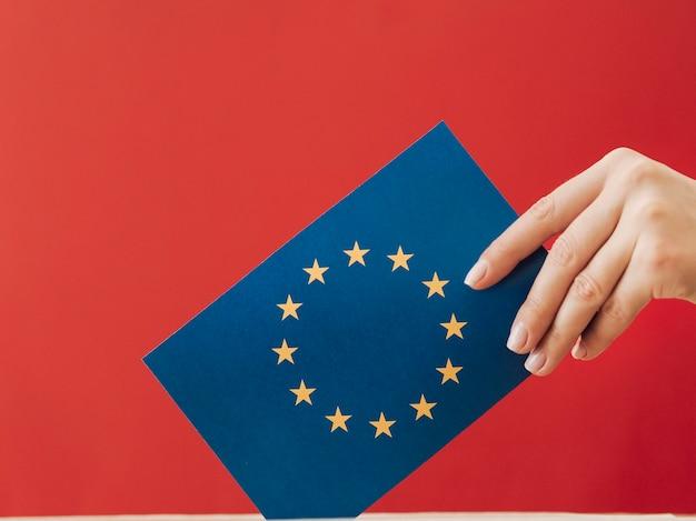 Vista lateral, mulher, pôr, um, europeu, votando, cartão, em, um, caixa Foto gratuita