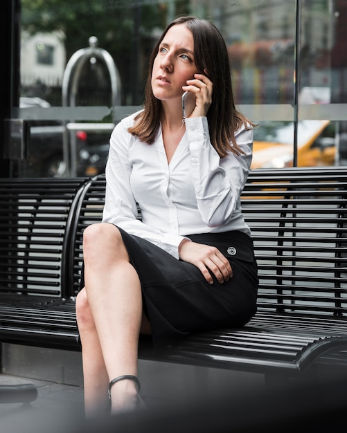Vista lateral, mulher, sentando, ligado, um, banco, com, telefone Foto gratuita