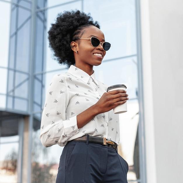 Vista lateral mulher sorridente com café ao ar livre Foto gratuita