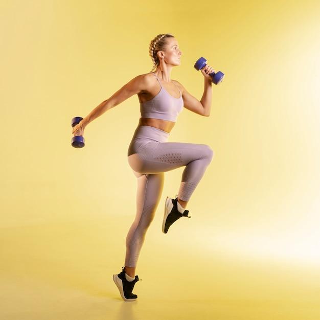 Vista lateral mulher treinando com pesos Foto gratuita
