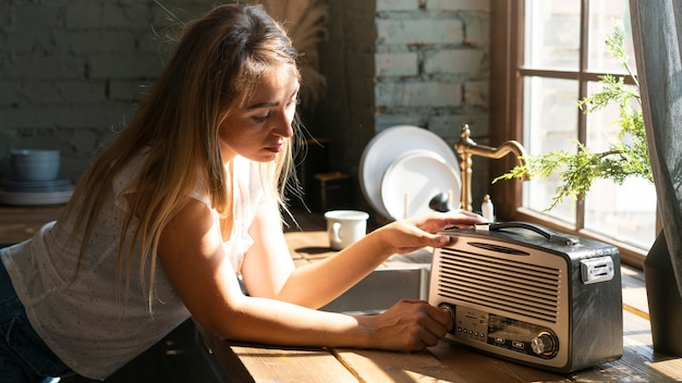 Vista lateral, mulher, usando, um, antigas, rádio Foto gratuita