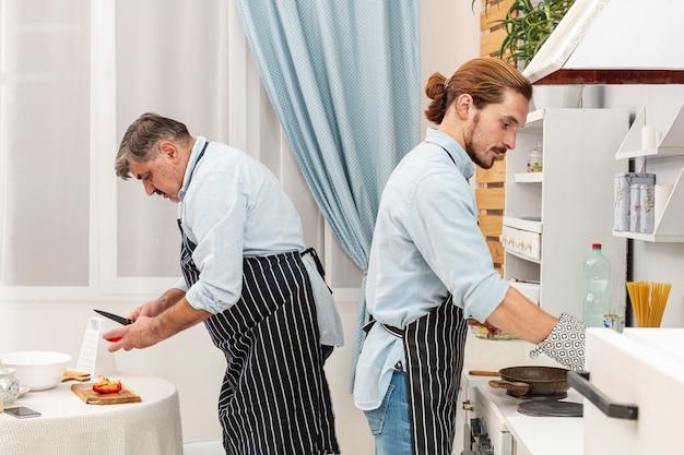 Vista lateral pai e filho cozinhar Foto gratuita