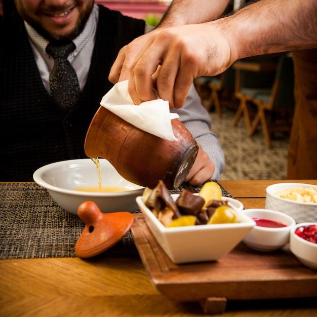 Vista lateral piti com prato fundo e vinagre e humanos em jarro de barro na mesa de madeira Foto gratuita