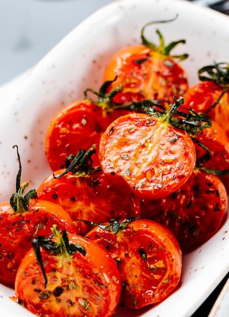Vista lateral próxima tomates secos ao sol em um prato Foto gratuita