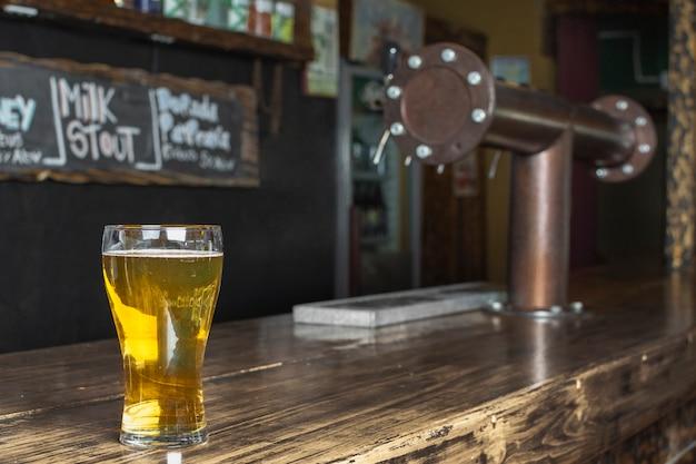 Vista lateral, refrescante copo com cerveja na mesa Foto gratuita