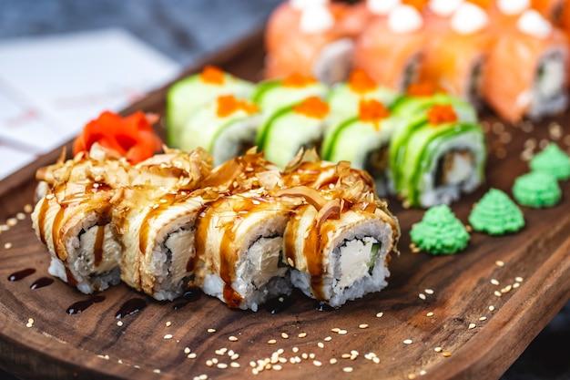 Vista lateral rolo de filadélfia com queijo creme de enguia conger pele de salmão seca molho de teriyaki sementes de gergelim e wasabi em uma placa Foto gratuita