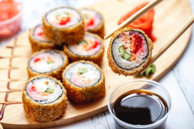 Vista lateral rolo quente rolo de sushi frito com creme de queijo pepino tomate salmão gengibre e wasabi em uma placa Foto gratuita