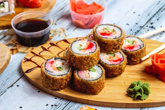 Vista lateral rolo quente rolo de sushi frito com tomate salmão pepino queijo creme de gengibre wasabi e molho de soja em cima da mesa Foto gratuita