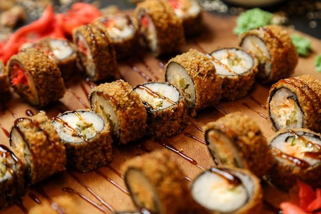 Vista lateral rolos de sushi frito em uma bandeja com gengibre e wasabi Foto gratuita
