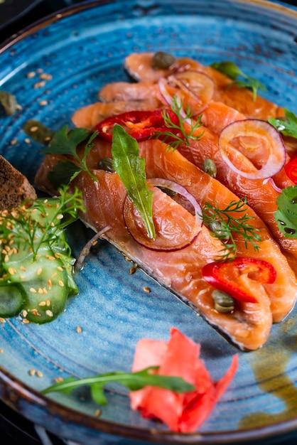Vista lateral salmão defumado com cebola pepino e ervas num prato azul Foto gratuita