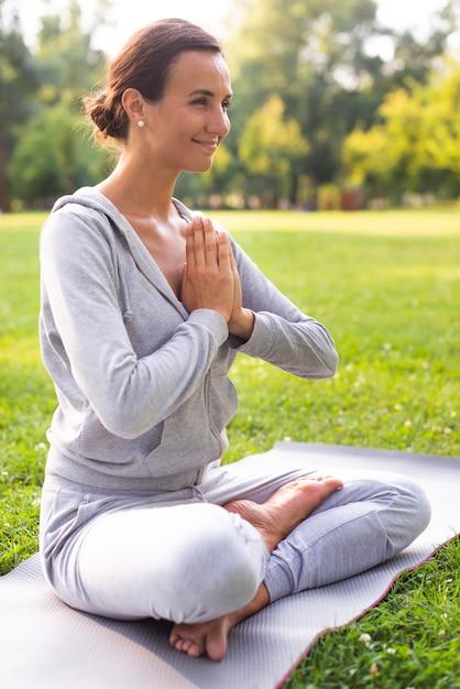 Vista lateral sorridente mulher meditando pose Foto gratuita