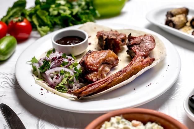 Vista lateral tike kebab no pão pita com ervas e cebolas com molho e legumes Foto gratuita
