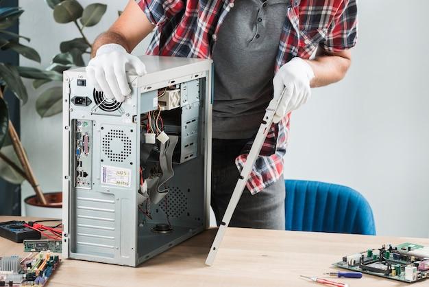 Vista mestra, de, um, macho, técnico, montagem, computador, ligado, escrivaninha madeira Foto gratuita