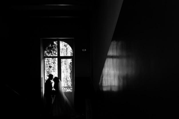Vista monocromática da silhueta do casal de noivos que está quase se beijando perto da janela Foto gratuita