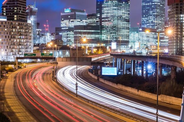 Vista noturna de cidade com arranha-céus e trilhas de semáforo Foto Premium