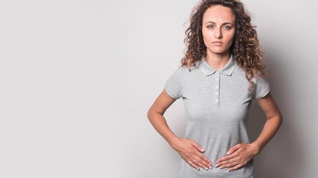 Vista panoramic, de, mulher jovem, tendo, estômago, dor, contra, experiência cinza Foto Premium