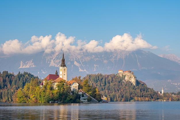 Vista panorâmica da ilha no lago bled com a igreja de peregrinação da assunção de maria, com reflexão. eslovênia, europa. Foto Premium