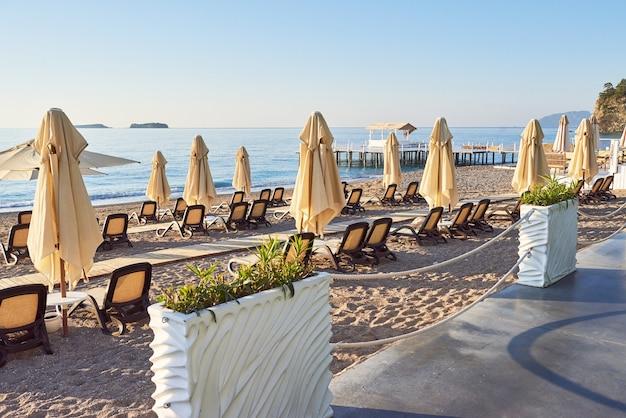 Vista panorâmica da praia privada com espreguiçadeiras e parasokamy o mar e as montanhas. recorrer. Foto gratuita