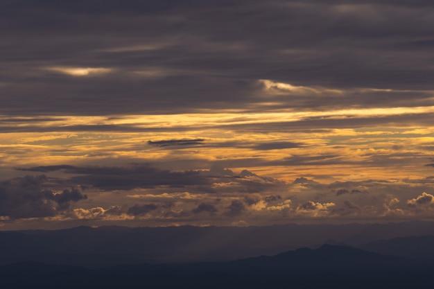 Vista panorâmica das montanhas de silhueta contra o céu durante o pôr do sol e feixe Foto Premium