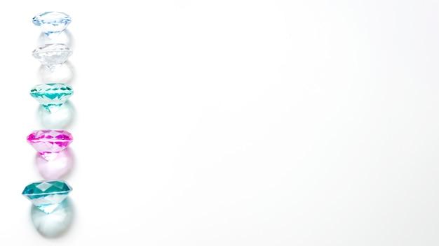 Vista panorâmica de diamantes coloridos brilhantes com sombra no fundo branco Foto gratuita