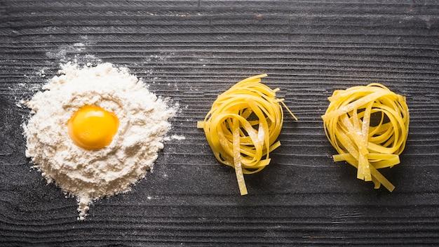 Vista panorâmica de gema de ovo com farinha branca e tagliatelle cru no contexto de madeira Foto gratuita
