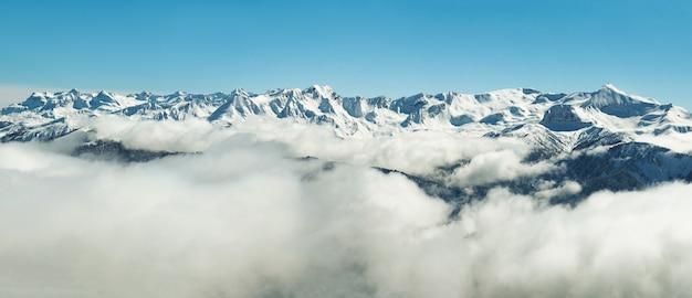 Vista panorâmica de montanhas nevadas de inverno em nuvens na abkházia ao fundo do céu azul Foto Premium