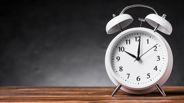 Vista panorâmica do despertador branco na mesa de madeira contra um fundo cinza Foto gratuita