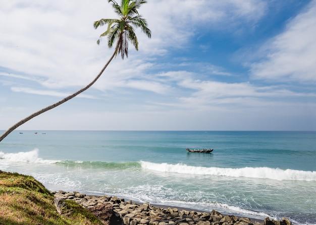 Vista para o mar com barcos de pescadores e palmeira na praia de odayam, índia Foto Premium