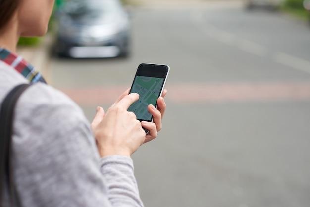 Vista por cima do ombro de uma pessoa irreconhecível que rastreia um táxi no aplicativo móvel Foto gratuita