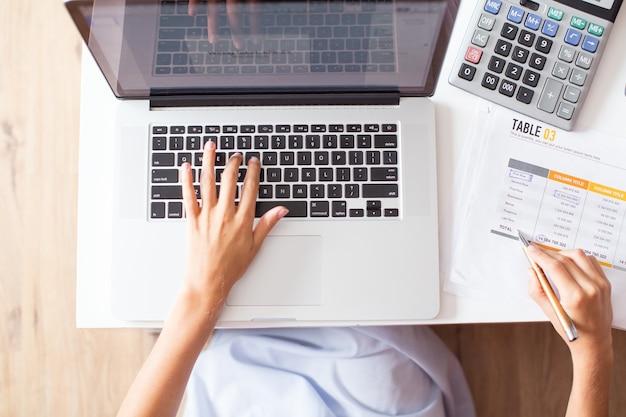 Vista recortada do contador trabalhando no laptop Foto gratuita