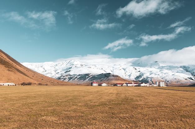 Vista serena do campo marrom com as casas de telhado vermelho e montanhas nevadas no Foto gratuita