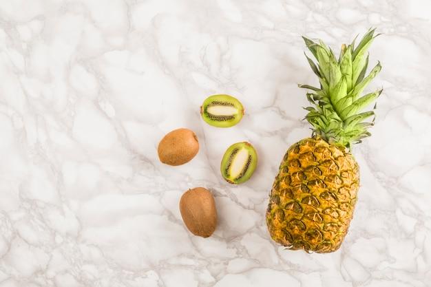 Vista superior abacaxi e kiwi em mármore Foto gratuita