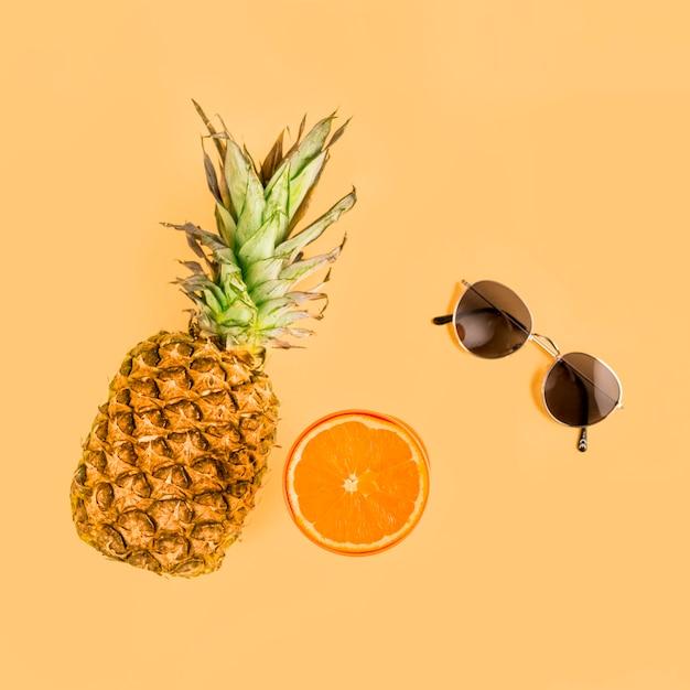Vista superior abacaxi, laranja e óculos de sol Foto gratuita