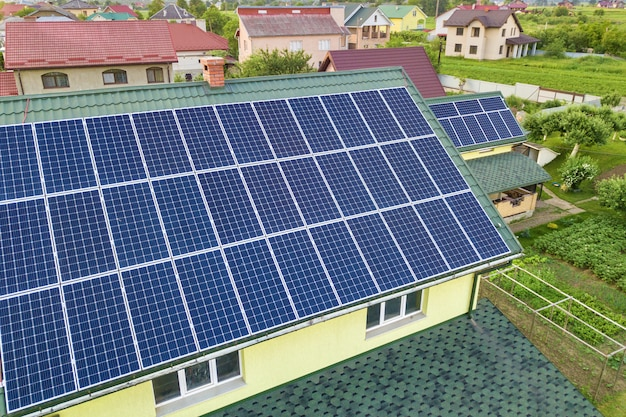 Vista superior aérea da nova casa residencial moderna casa com sistema de painéis solares foto brilhante azul solar no telhado. conceito de produção de energia verde ecológica renovável. Foto Premium