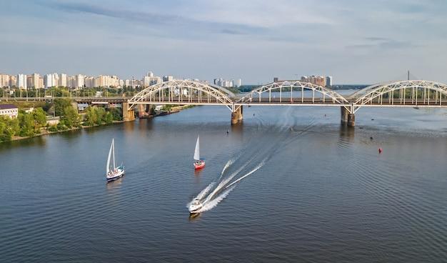 Vista superior aérea da ponte de darnitsky, iates e barcos navegando no rio dnieper Foto Premium