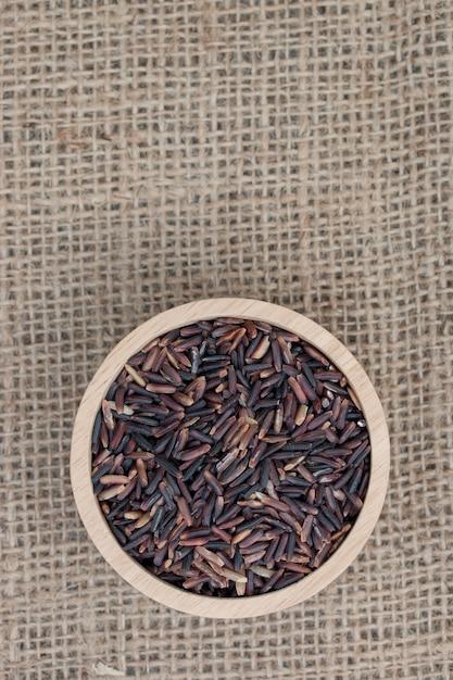 Vista superior: arroz integral (baga do arroz) na bacia de madeira na textura do saco. Foto Premium