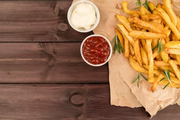 Vista superior batatas fritas com molho na mesa de madeira Foto gratuita