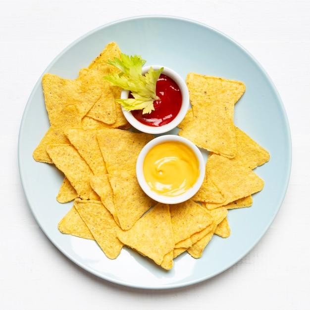 Vista superior batatas fritas e molho no prato Foto gratuita