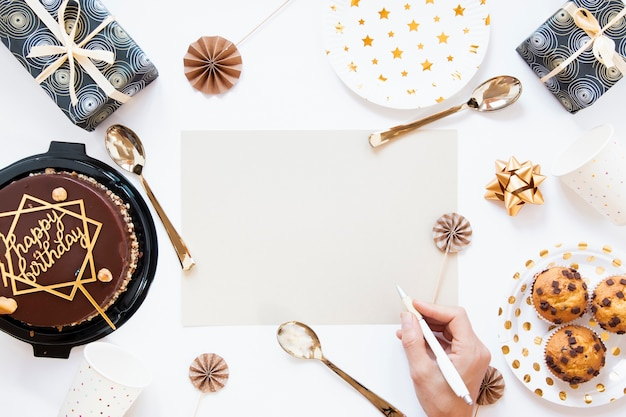 Vista superior bolo de aniversário e biscoitos com convite de aniversário vazio Foto gratuita