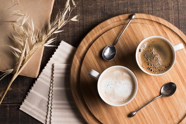 Vista superior café e café com leite em canecas brancas na placa de madeira Foto gratuita