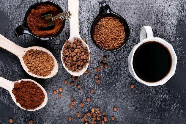 Vista superior café instantâneo em colheres de pau e xícara de café na superfície escura Foto gratuita