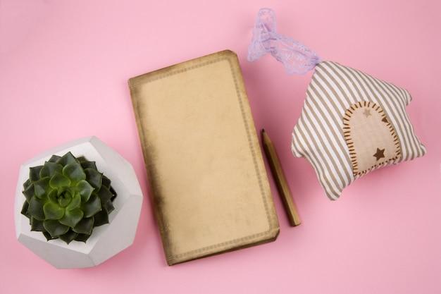 Vista superior casa de brinquedo de pelúcia, caderno vintage vazio e pote de concreto suculento Foto Premium