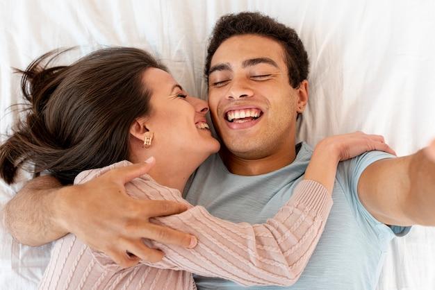 Vista superior casal feliz tomando uma selfie Foto gratuita