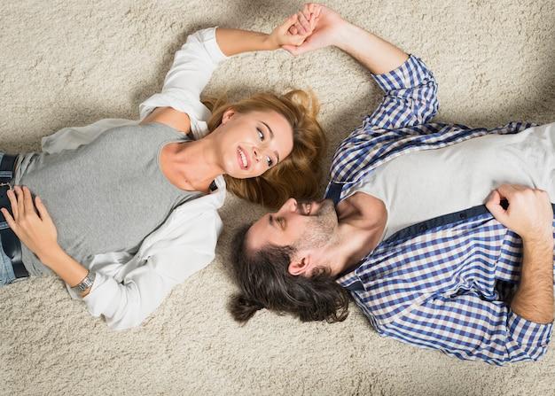 Vista superior casal retrato deitado no tapete Foto gratuita