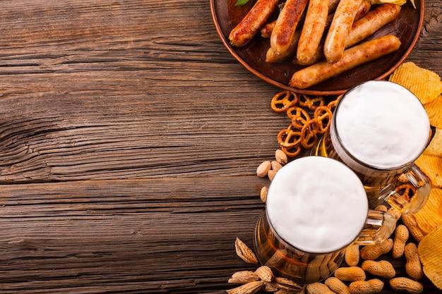 Vista superior cerveja com comida na mesa de madeira Foto gratuita
