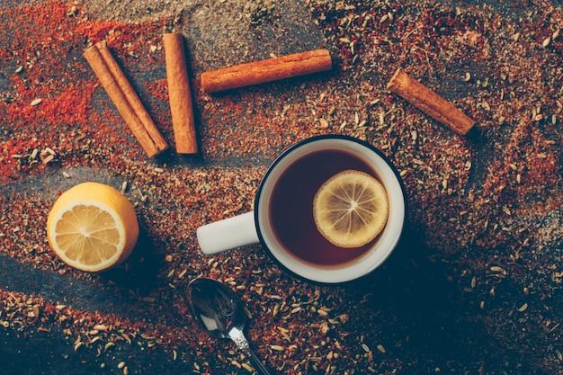 Vista superior, chá de limão e ervas secas com canela seca, colher e limão Foto gratuita